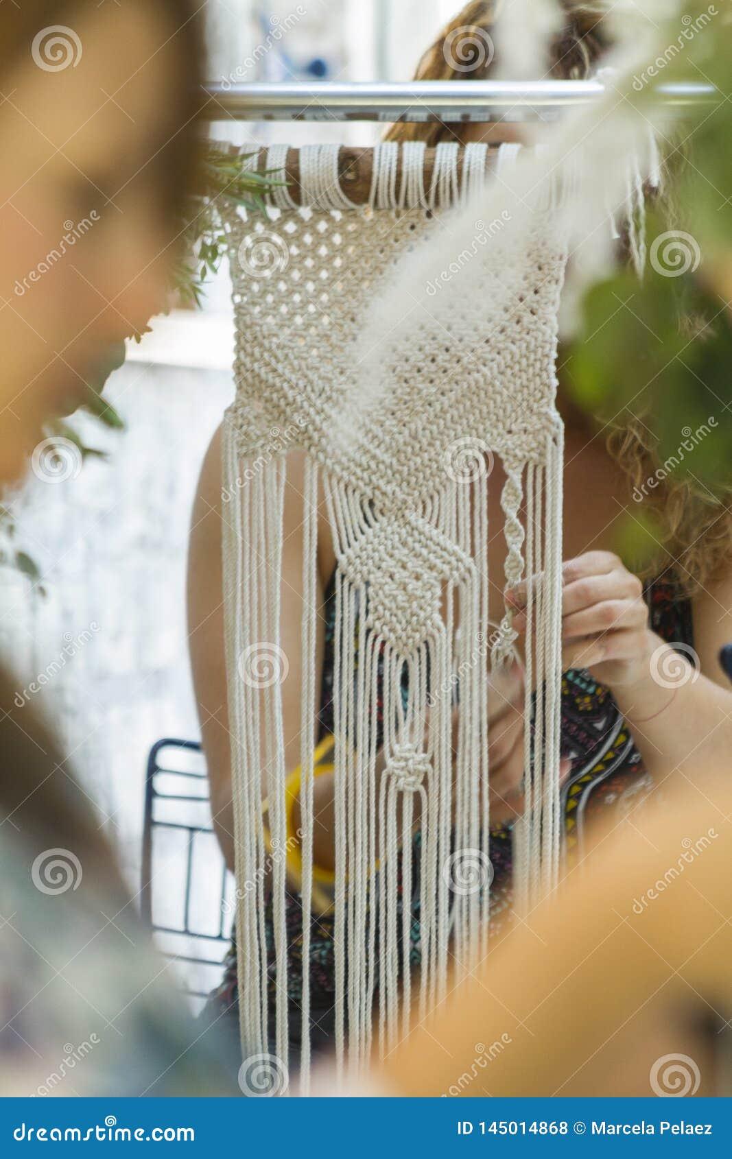 Mão que tece a tapeçaria bege do macramê do fio