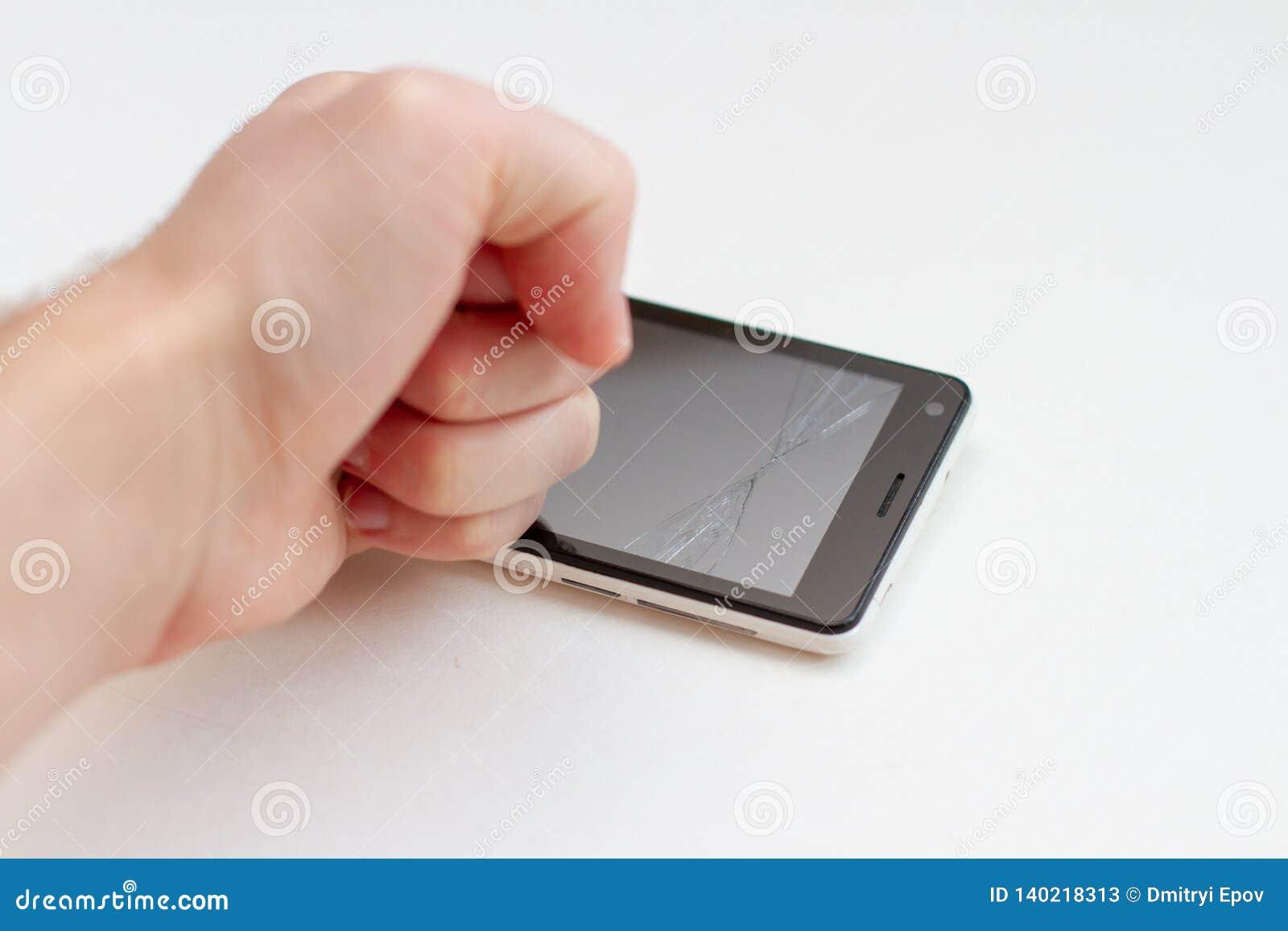 A mão quebra o smartphone no fundo branco