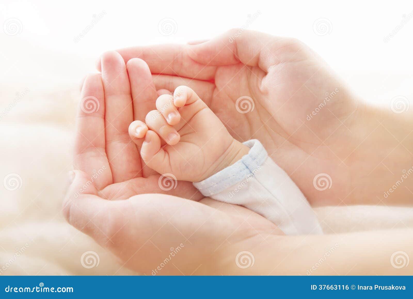 Mão recém-nascida do bebê nas mãos da mãe. Conceito do asistance da ajuda