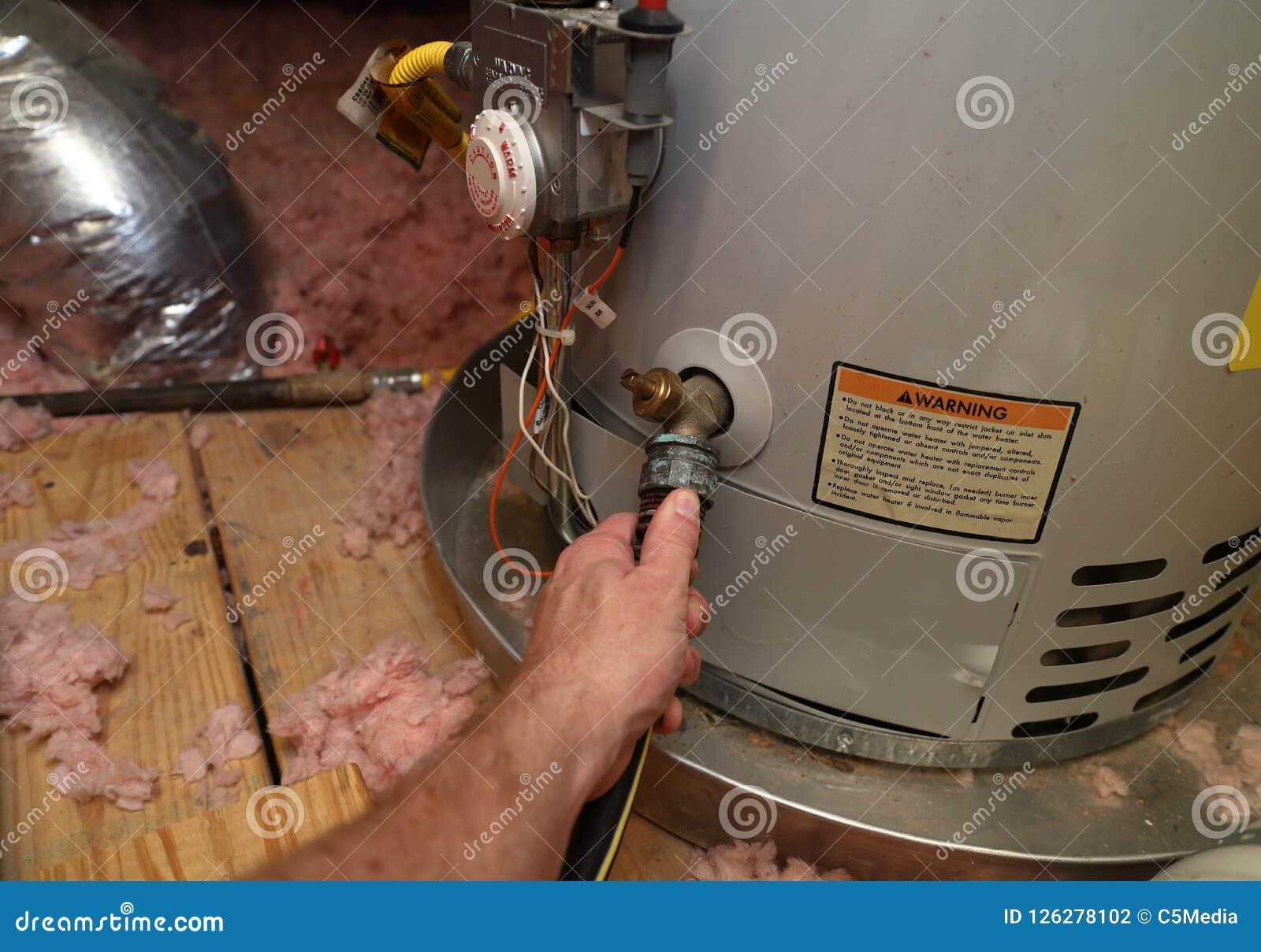 A mão une a mangueira ao aquecedor de água do dreno