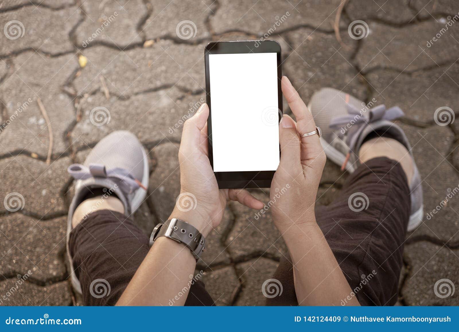 Mão usando a rua urbana do telefone celular