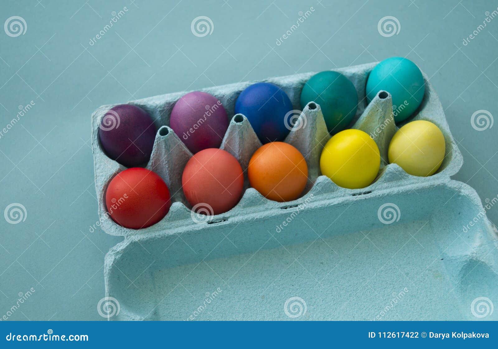 Mão vibrante ovos da páscoa coloridos tingidos em uma caixa de ovo do cartão vista