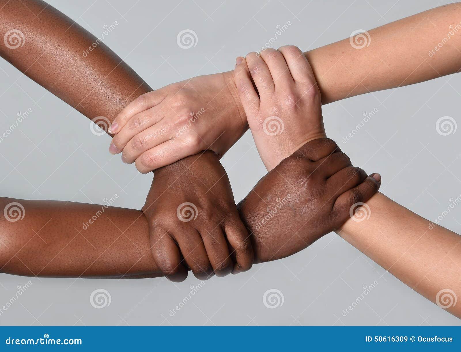Mãos americanas caucasianos brancas da fêmea e do africano negro que mantêm-se unidas contra o racismo e a xenofobia