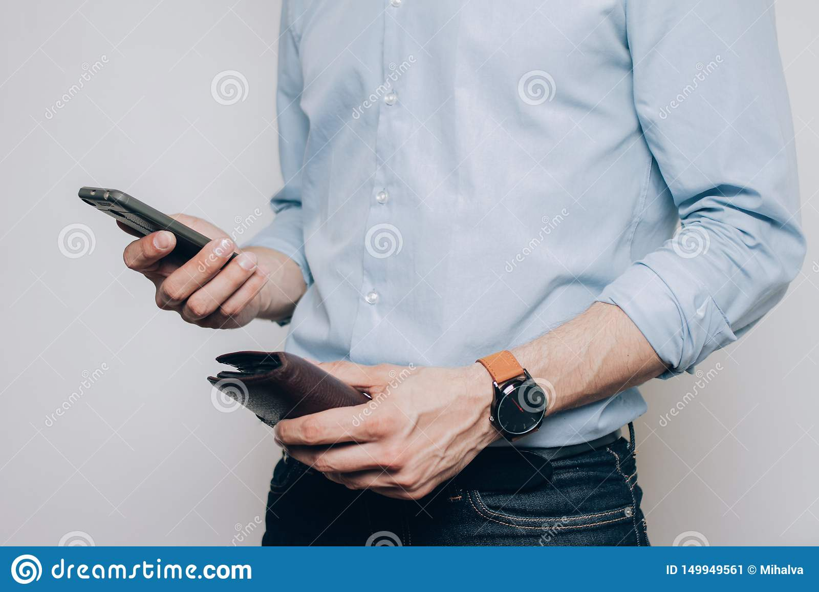 Mãos com carteira e o telefone marrons