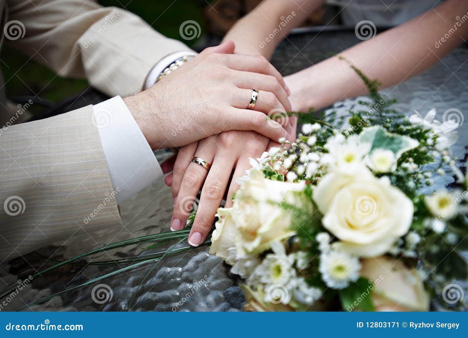 Mãos com os newlyweds dos anéis de casamento