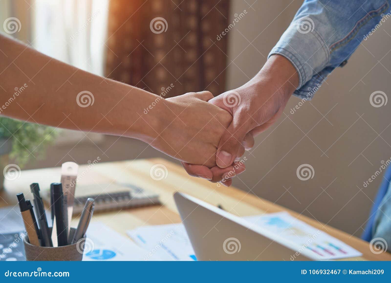 Mãos comum de dois homens de negócios após ter negociado um acordo bem sucedido do negócio, e o aperto de mão junto