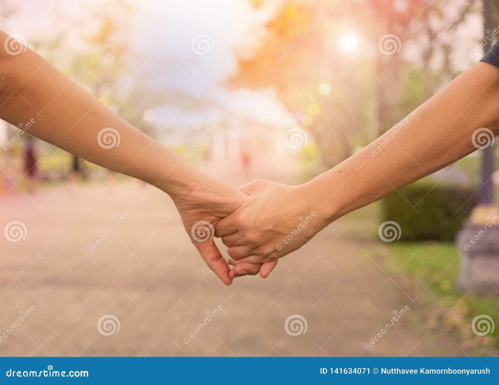 Mãos da agitação da terra arrendada da mulher e do homem,