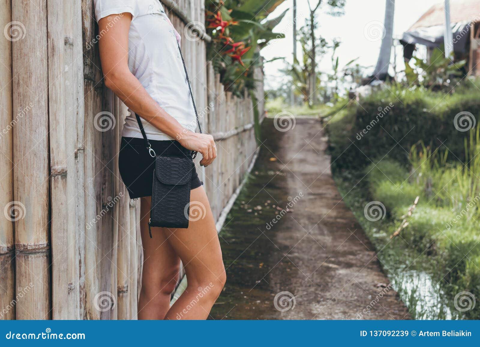 Mãos da jovem mulher com a bolsa luxuosa à moda do pitão do snakeskin fora Ilha de Bali