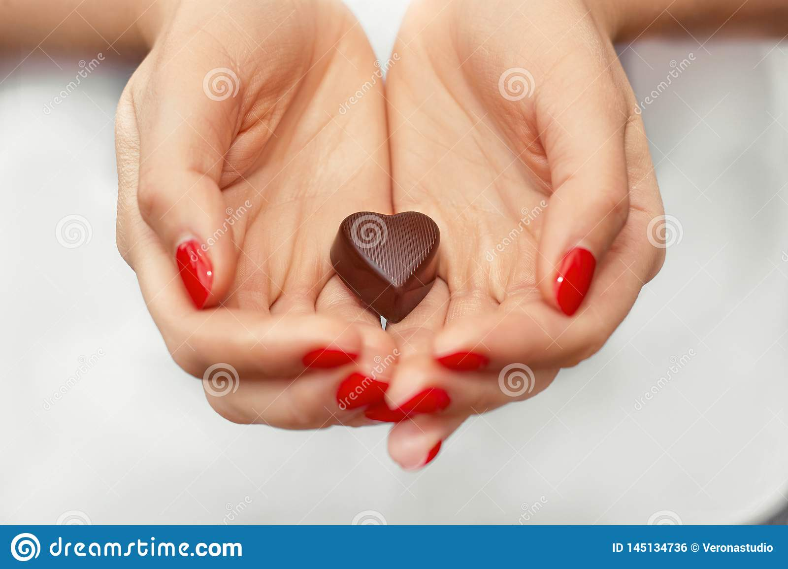 Mãos da jovem mulher com chocolate escuro em uma forma de um coração Aprecie o estilo de vida saud?vel Doces de chocolate Dias fe