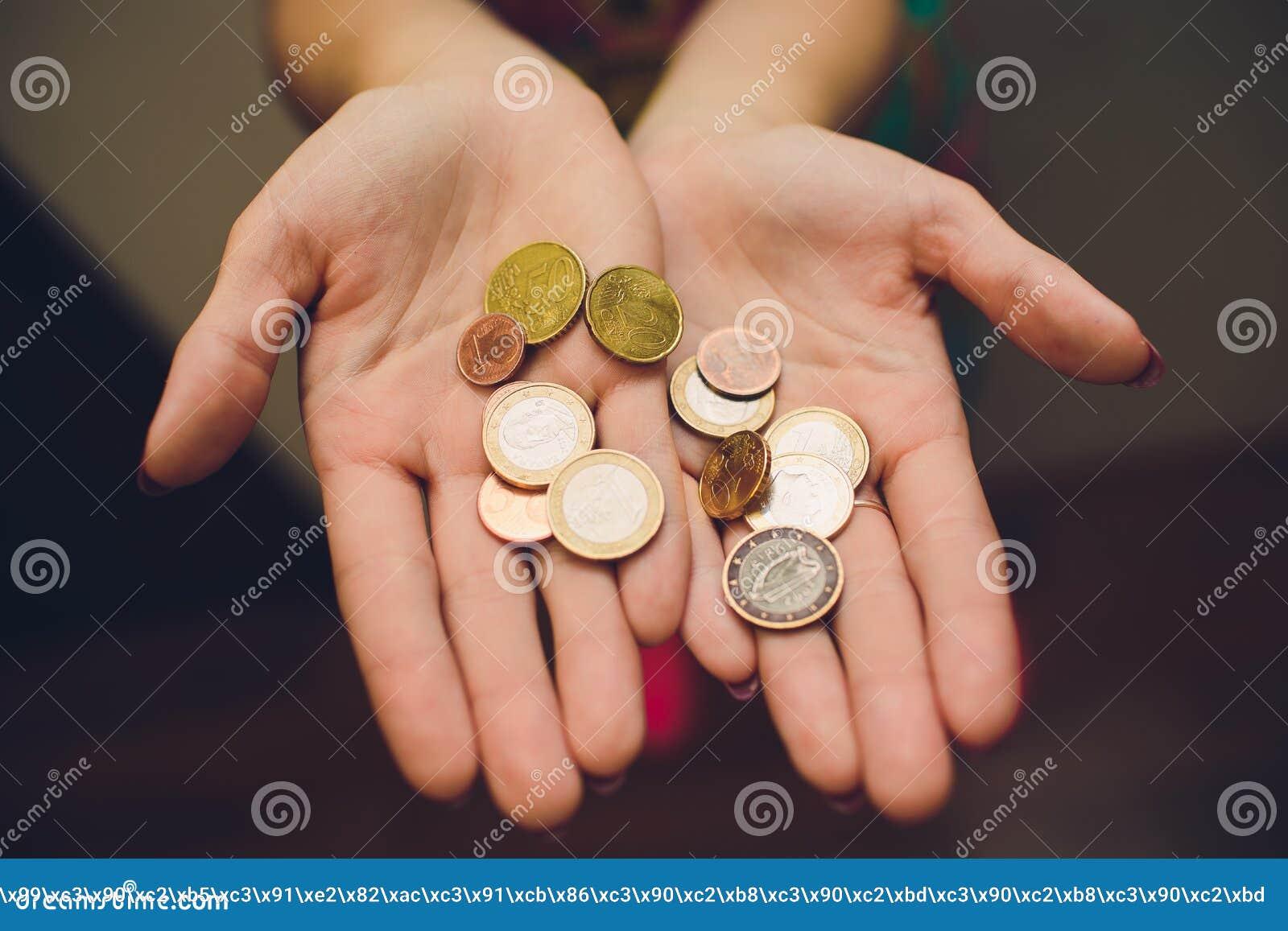 Mãos da jovem mulher que guardam o frasco de vidro com dinheiro, vista superior, com espaço da cópia