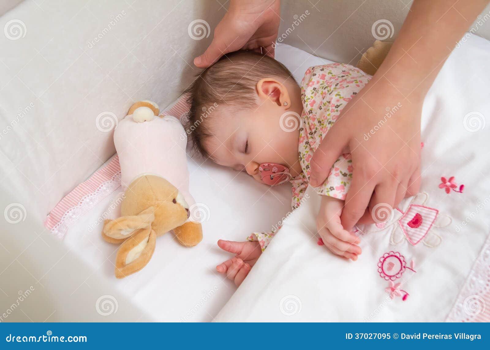 Mãos da mãe que acariciam seu sono do bebê