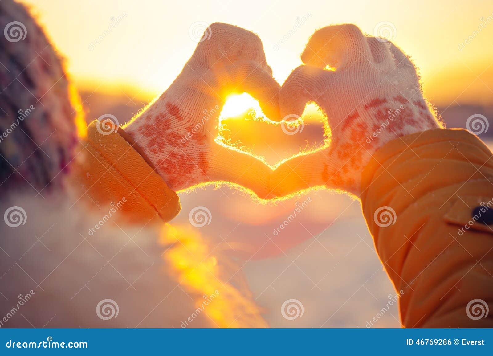 Mãos da mulher no símbolo do coração das luvas do inverno dado forma
