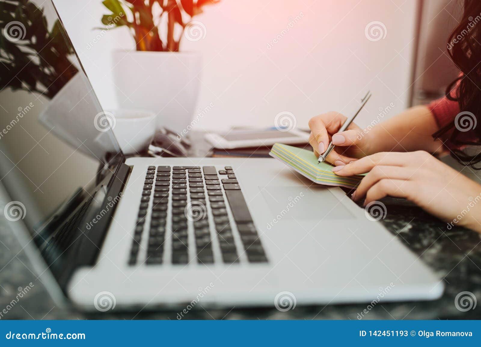 Mãos da mulher que escrevem na frente do portátil