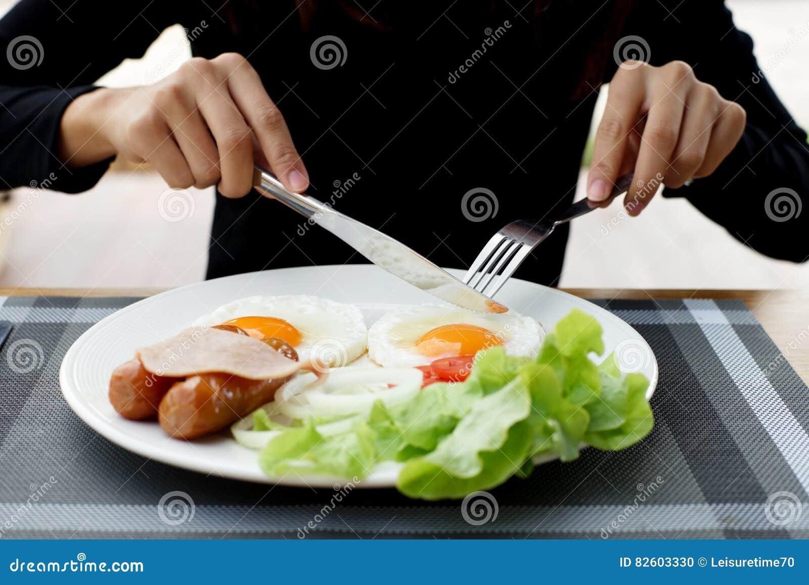 Mãos da mulher que guardam a faca e a forquilha durante comer o café da manhã
