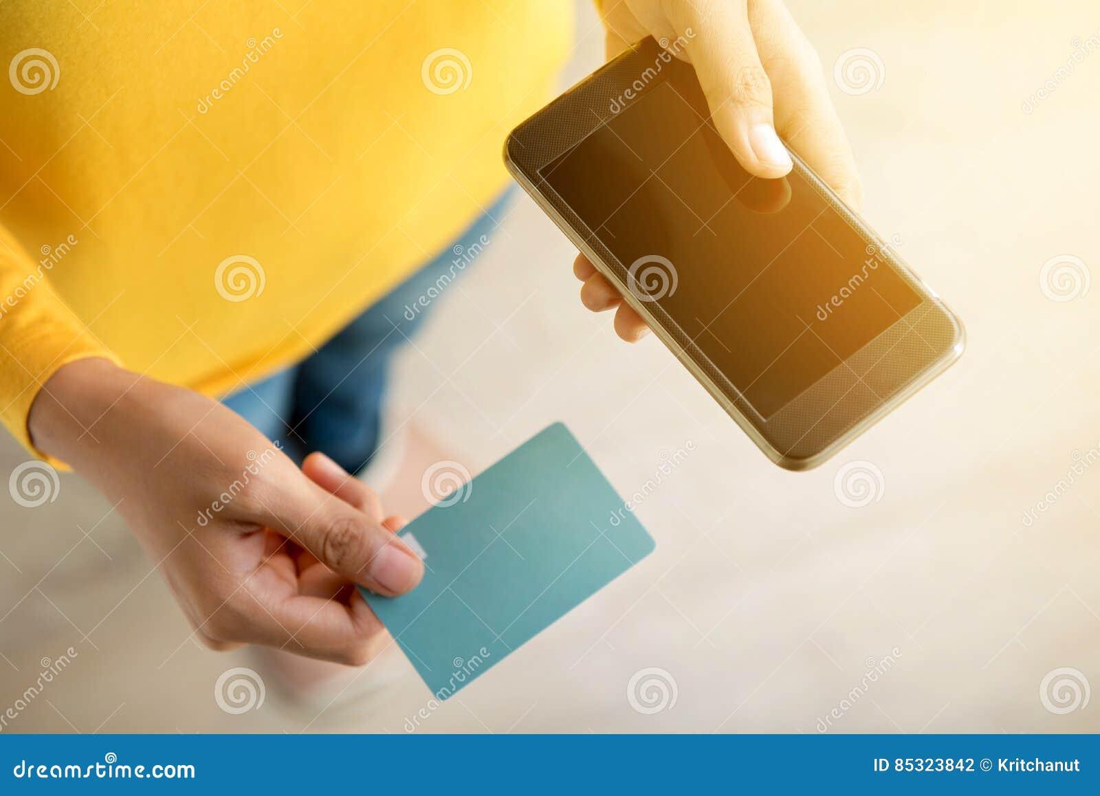 Mãos da mulher que guardam o smartphone e o cartão de crédito