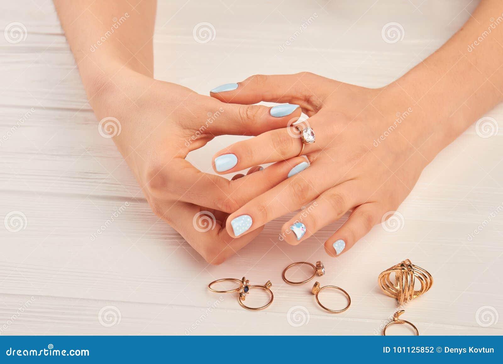 Mãos da mulher que põem sobre o anel dourado