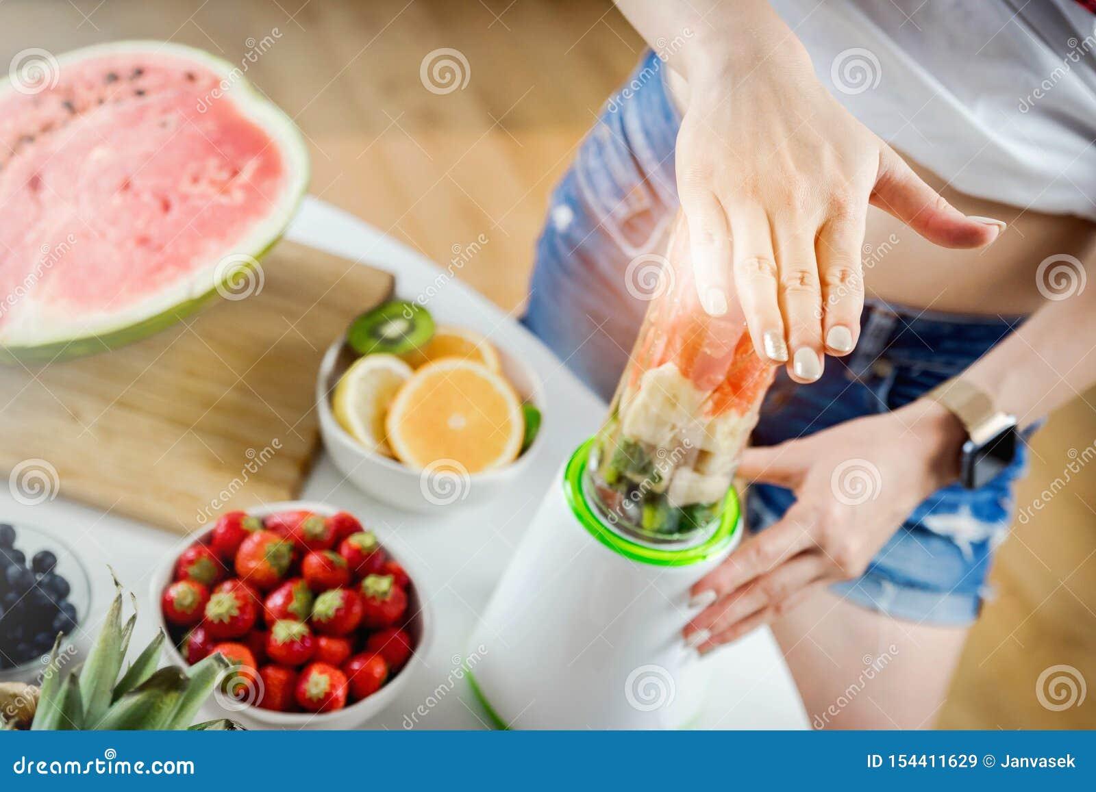 Mãos da mulher que preparam o suco de fruta do batido