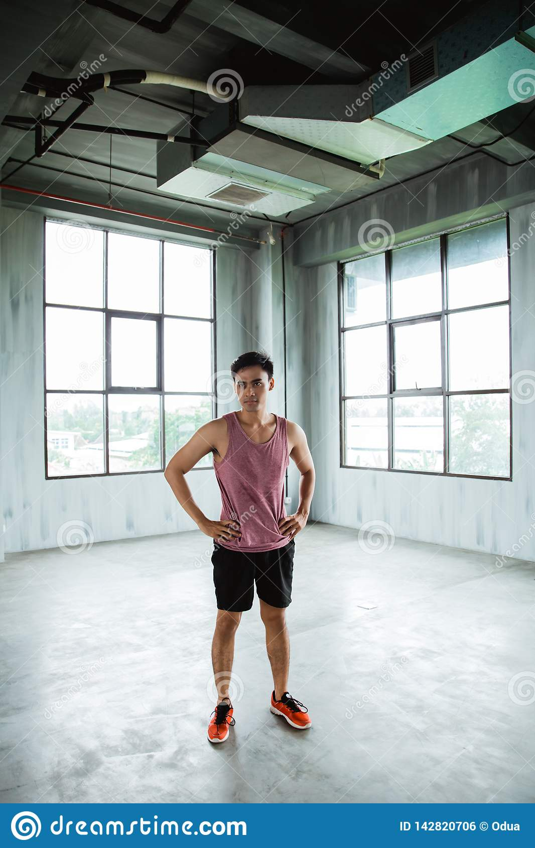 Mãos da pose da cintura do desportista asiático ao descansar após o exercício