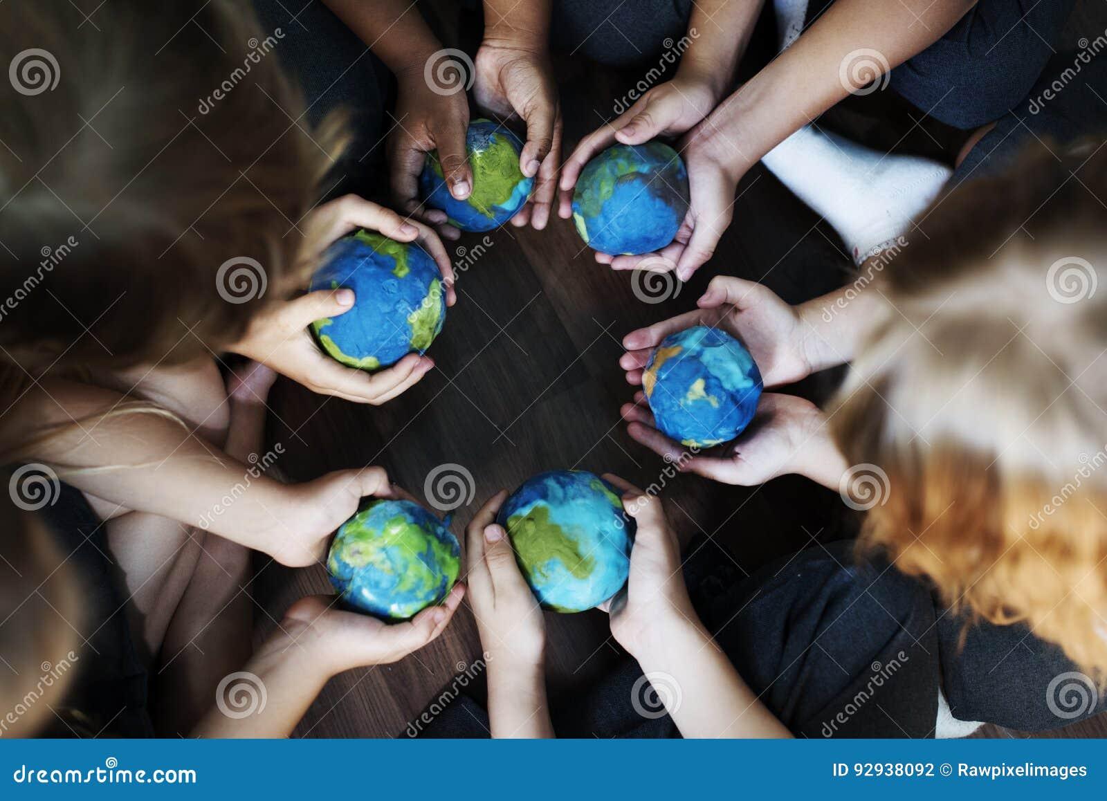 Mãos das crianças que mantêm as bolas colocando do globo unidas