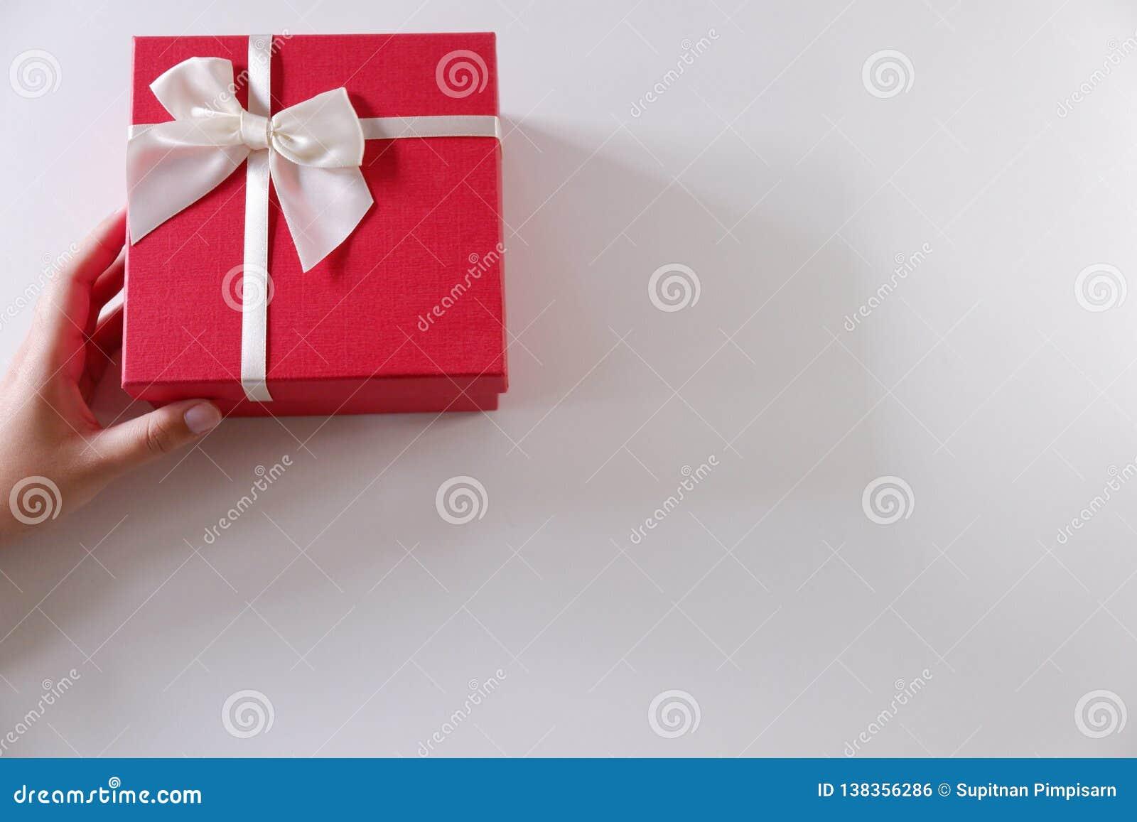 Mãos das mulheres do close-up que enviam a caixa de presente vermelha com a fita branca no fundo branco