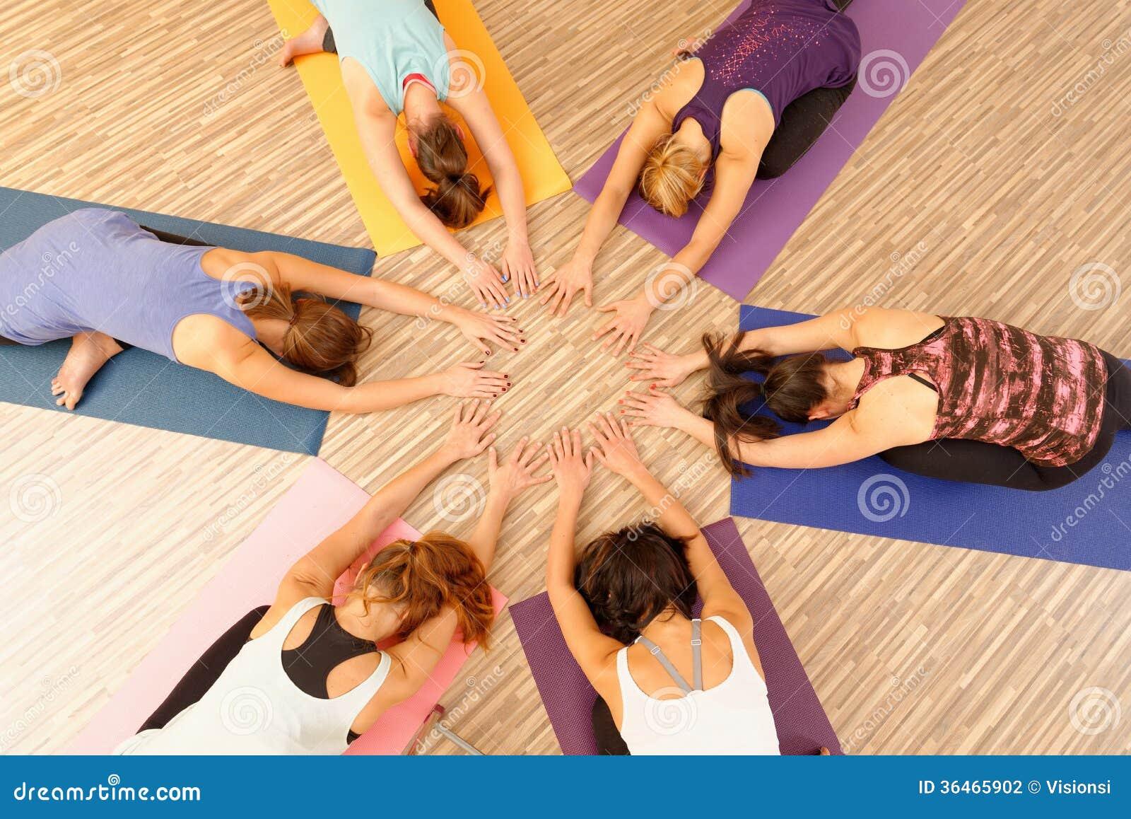 Mãos das mulheres que formam a ioga do círculo/fluxo de Vinyasa