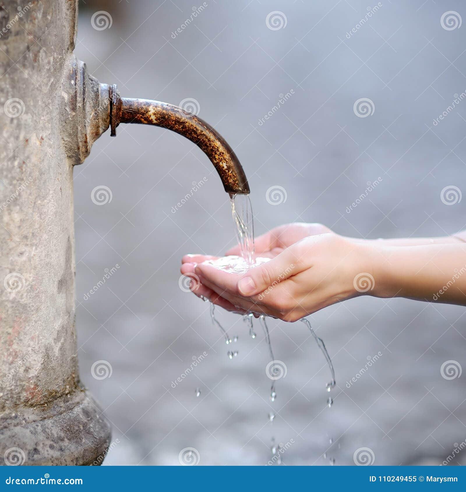 Mãos de lavagem da mulher em uma fonte da cidade em Roma, Itália