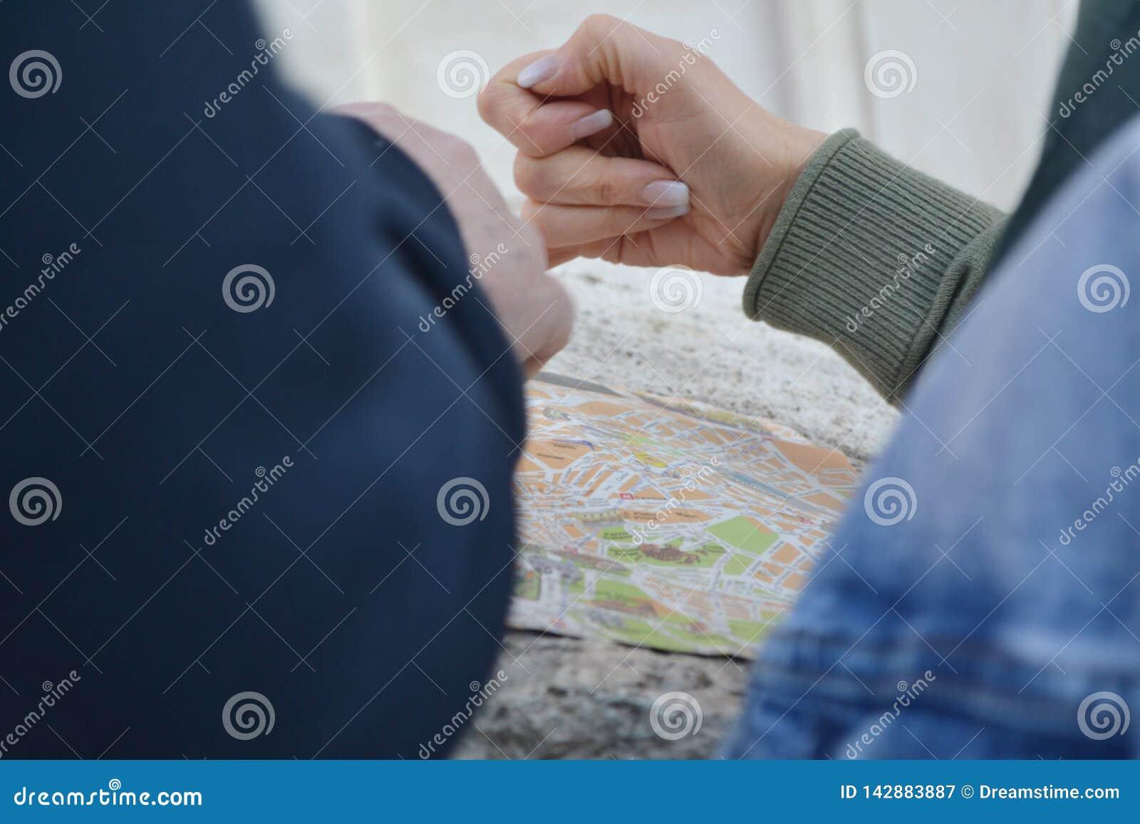 Mãos de Peaple que choicing a maneira no mapa de viagem