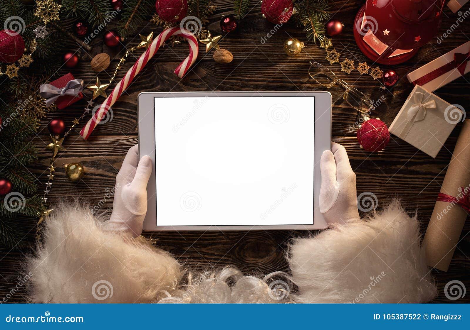 Mãos de Santa Claus que guardam a tabuleta digital vazia