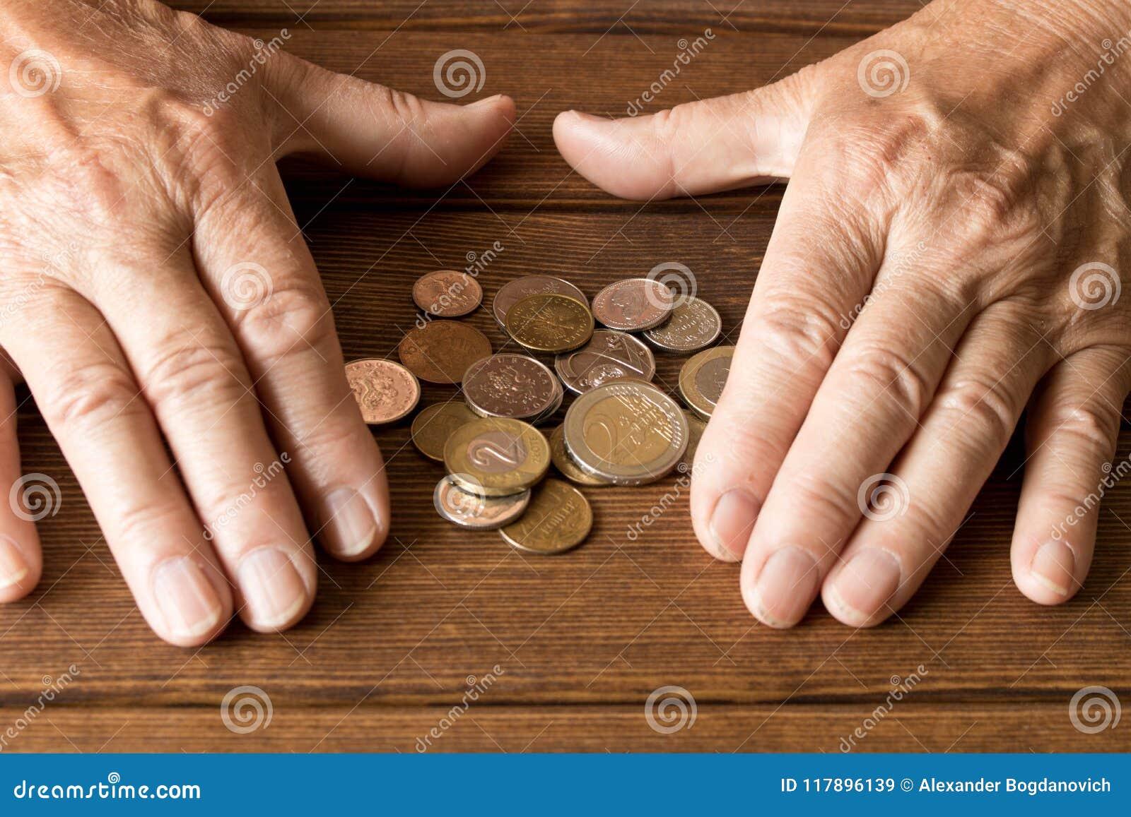 Mãos de um homem idoso com várias moedas em uma tabela de madeira Th