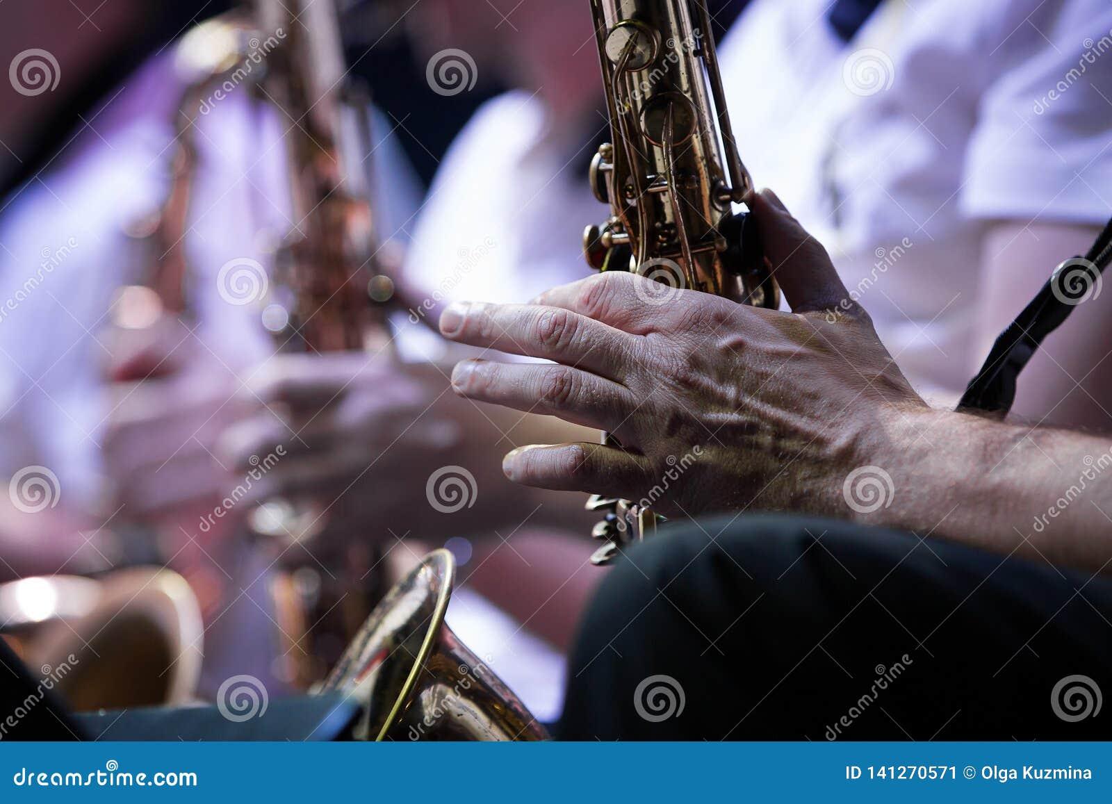 Mãos de um músico Jogadores de saxofone, concerto Close-up