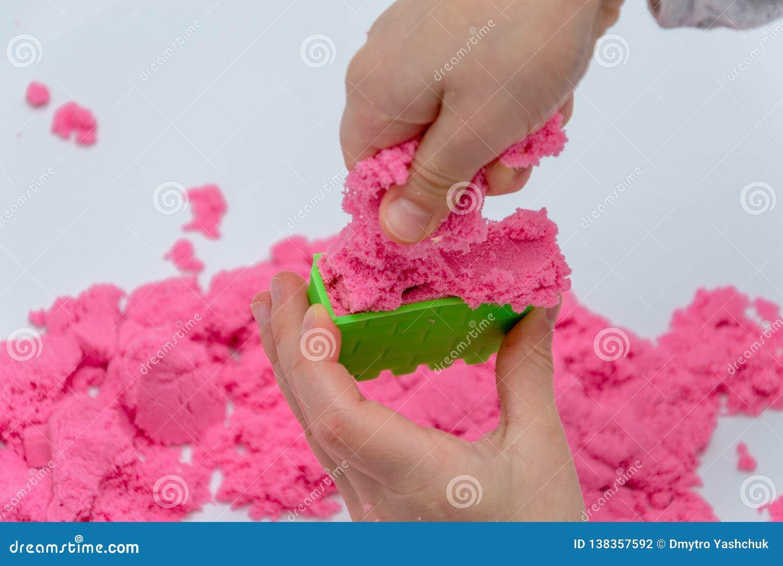 Mãos de uma criança que joga com a areia mágica cor-de-rosa