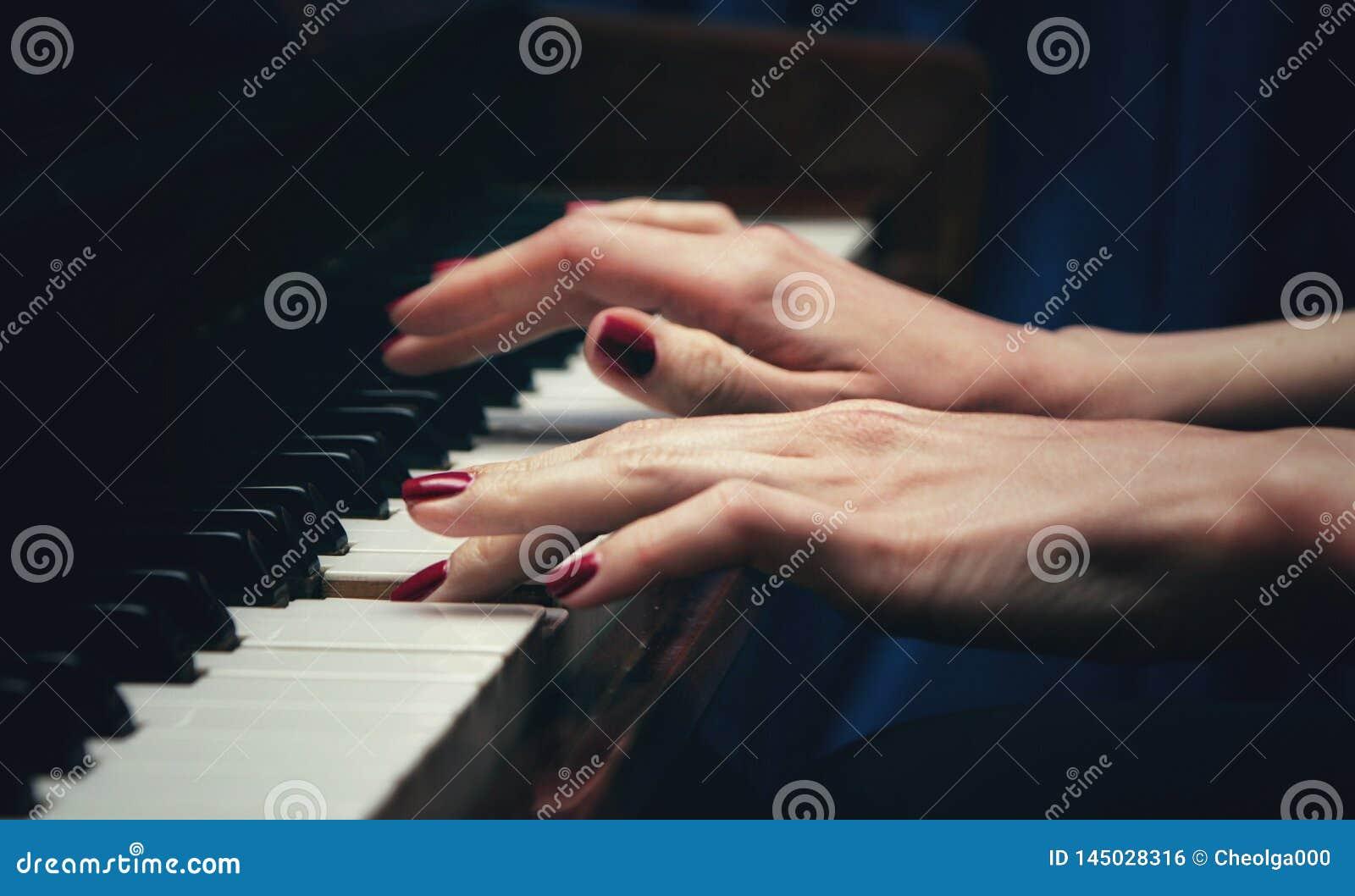 M?os de uma jovem mulher bonita que joga o piano Vista lateral Foco seletivo spaceBlur da c?pia
