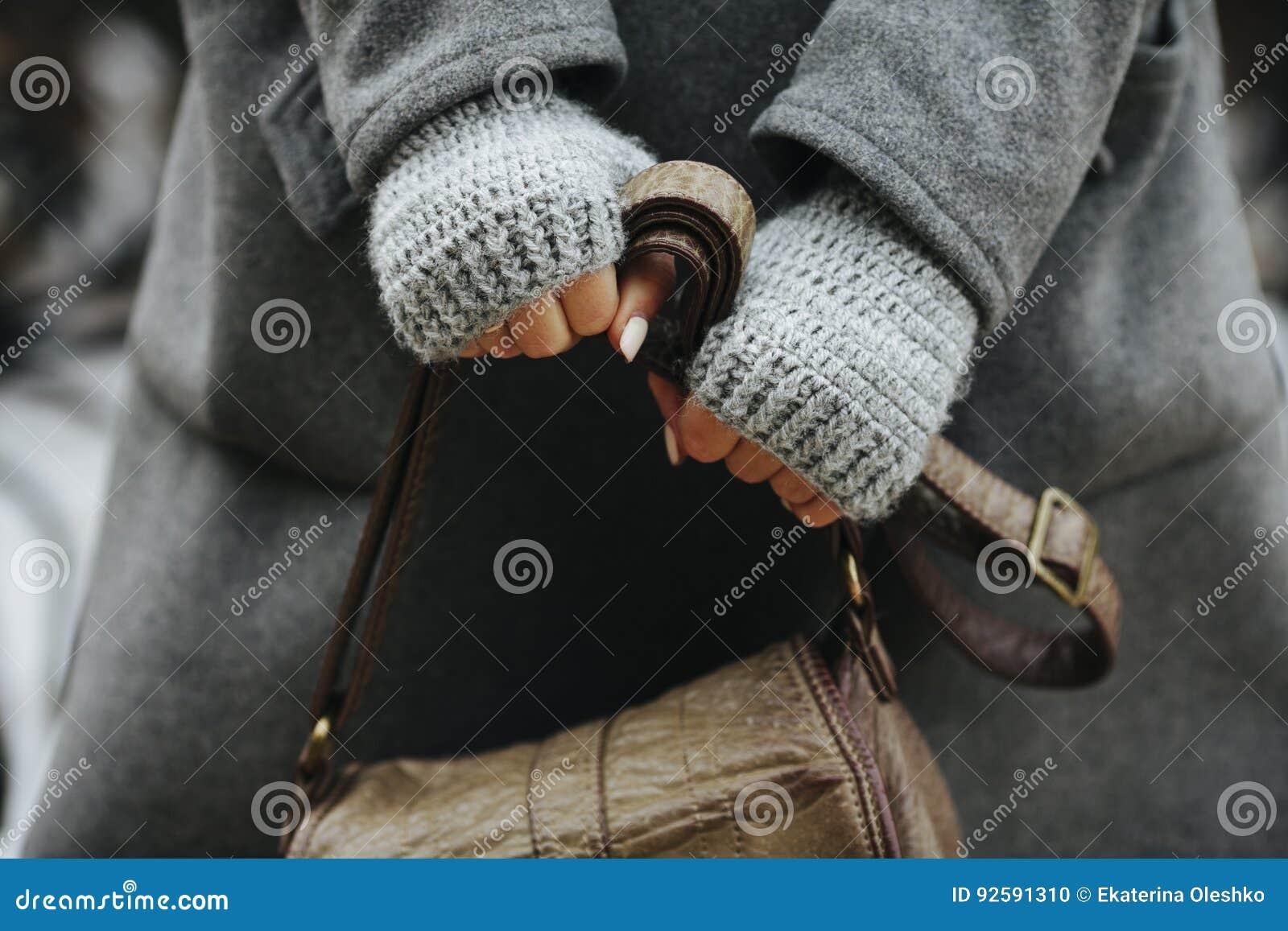 Mãos de uma menina que guarda um saco, outono, mola