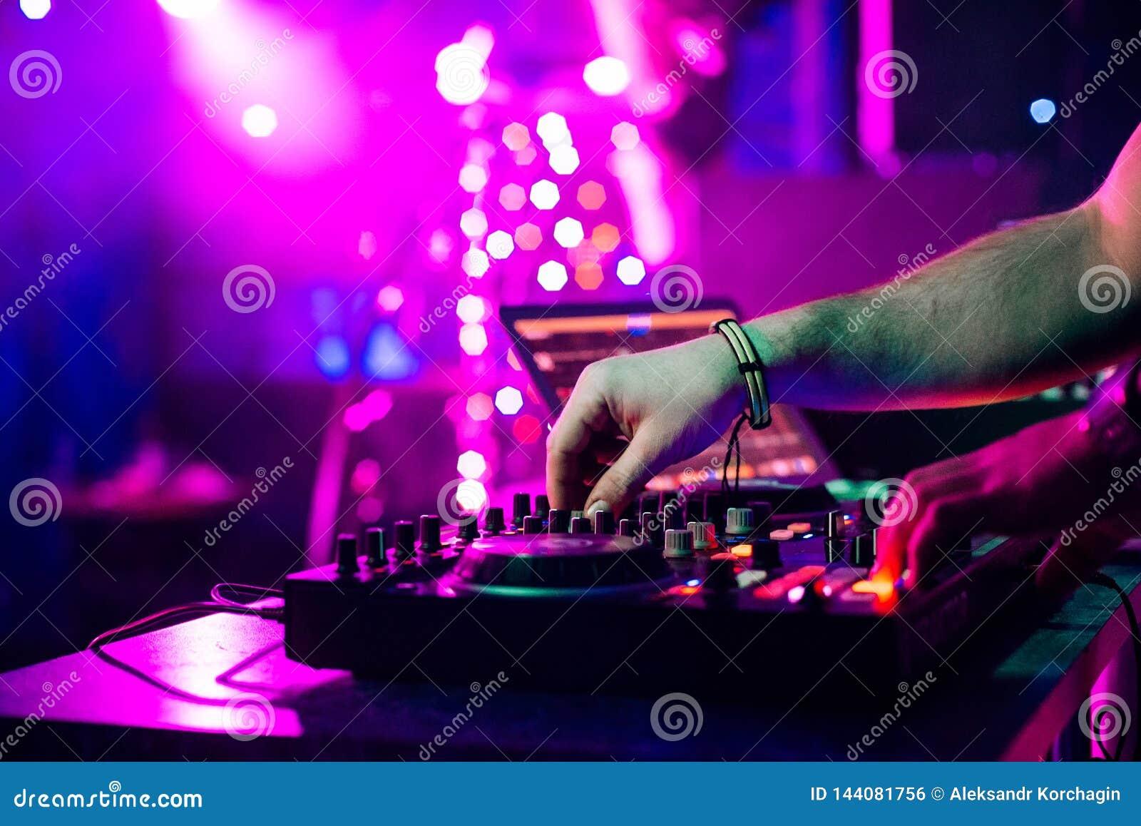 Mãos DJ que misturam e que jogam a música em um misturador profissional do controlador