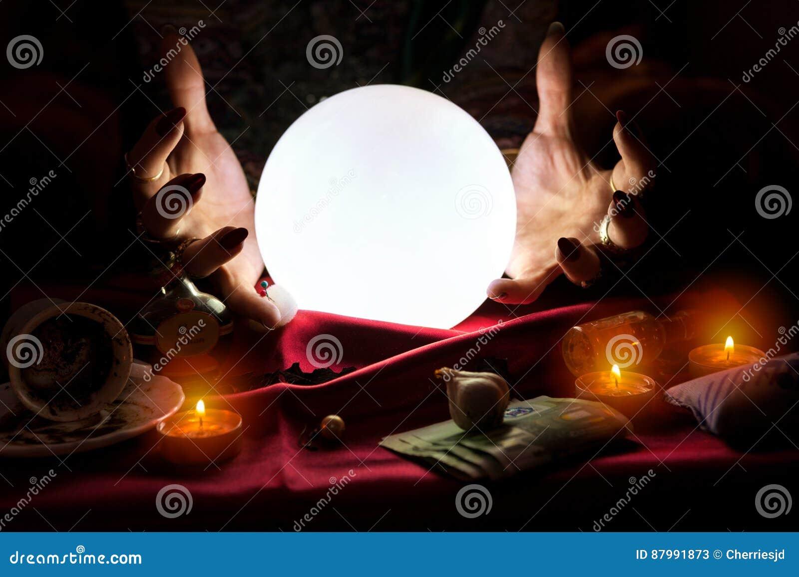 Mãos do caixa de fortuna com bola de cristal no meio