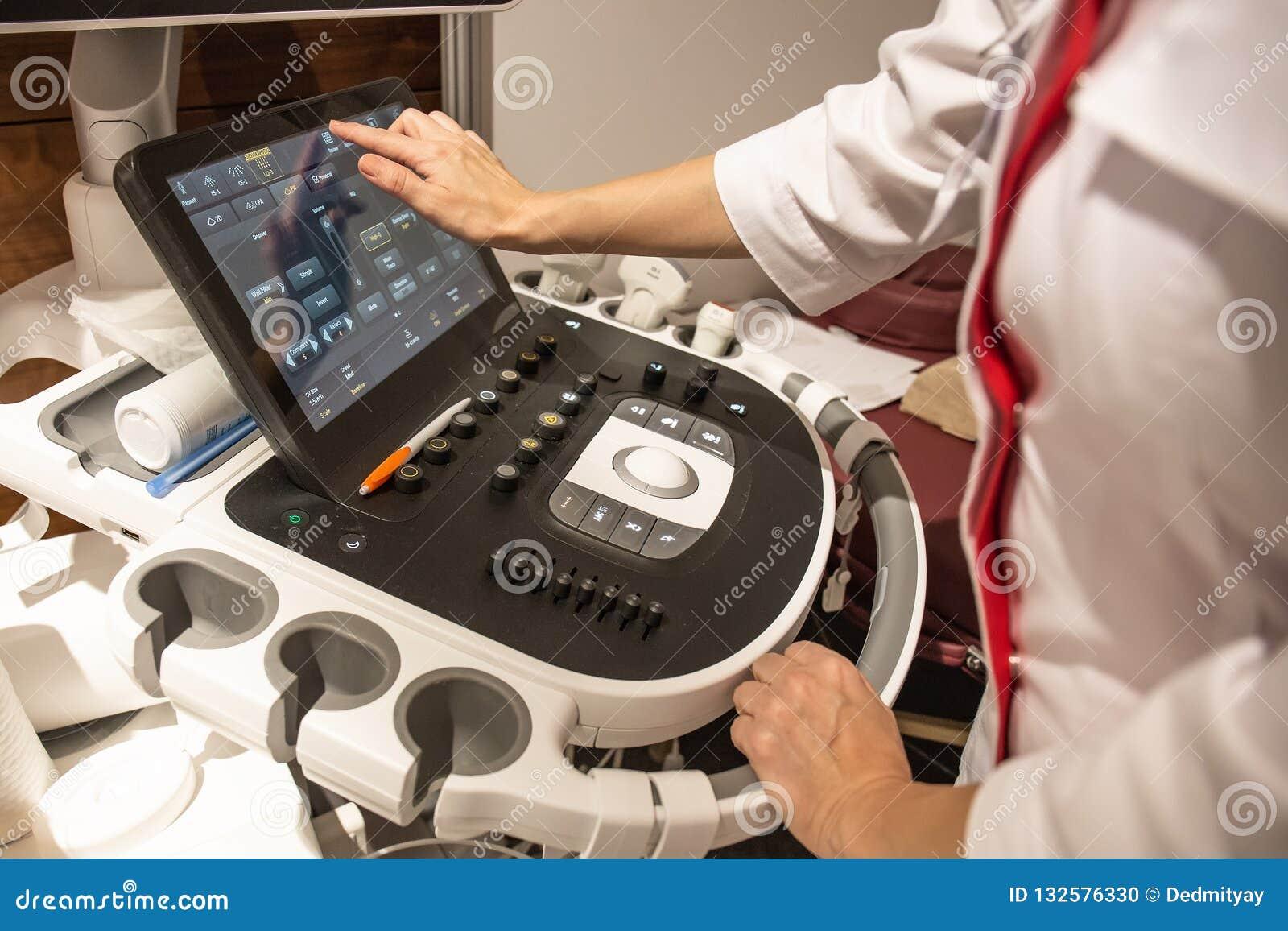 Mãos do doutor no painel de controle com o teclado do equipamento diagnóstico do ultrassom médico na clínica