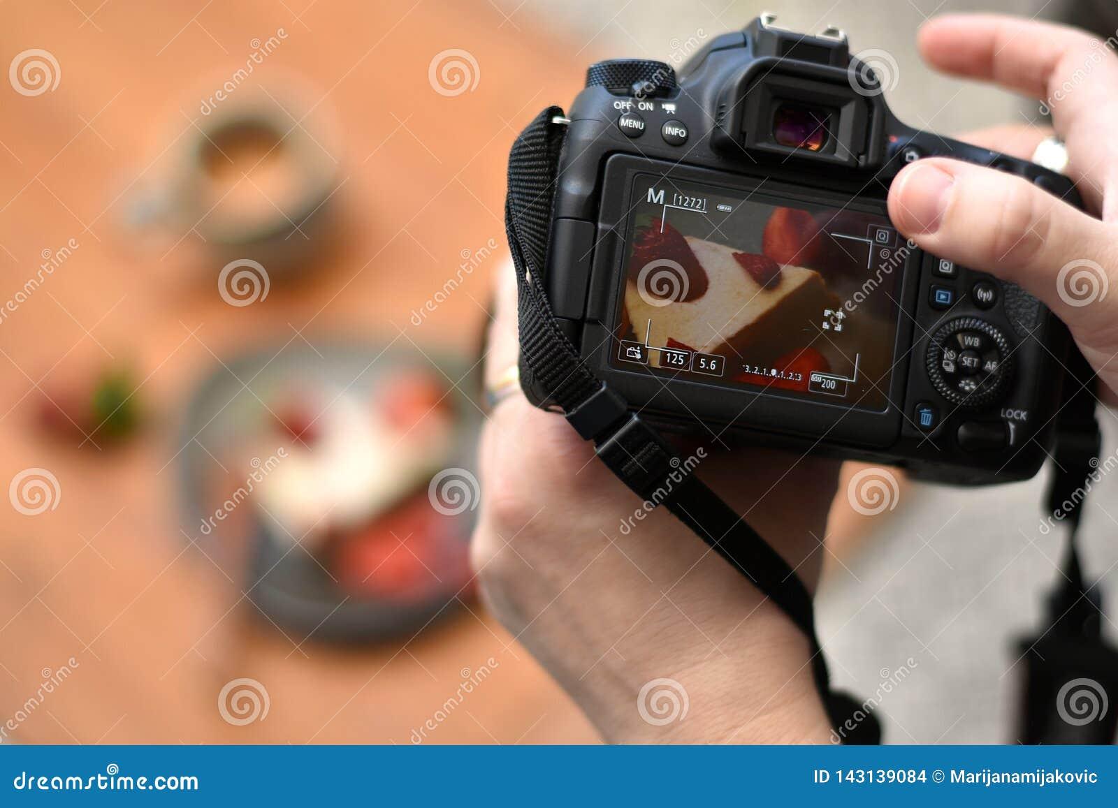 Mãos do fotógrafo que guardam a câmera do dslr que toma uma foto