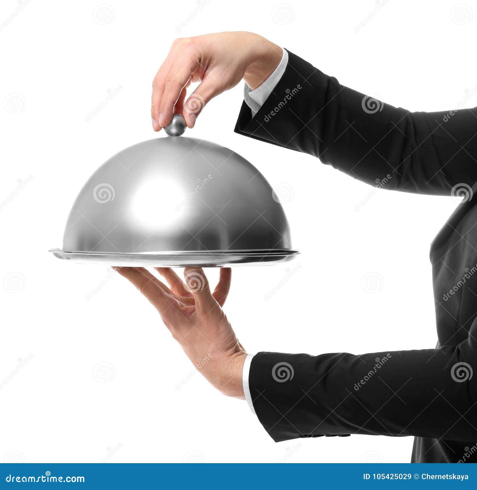 Mãos do garçom que guardam a bandeja do metal com tampa