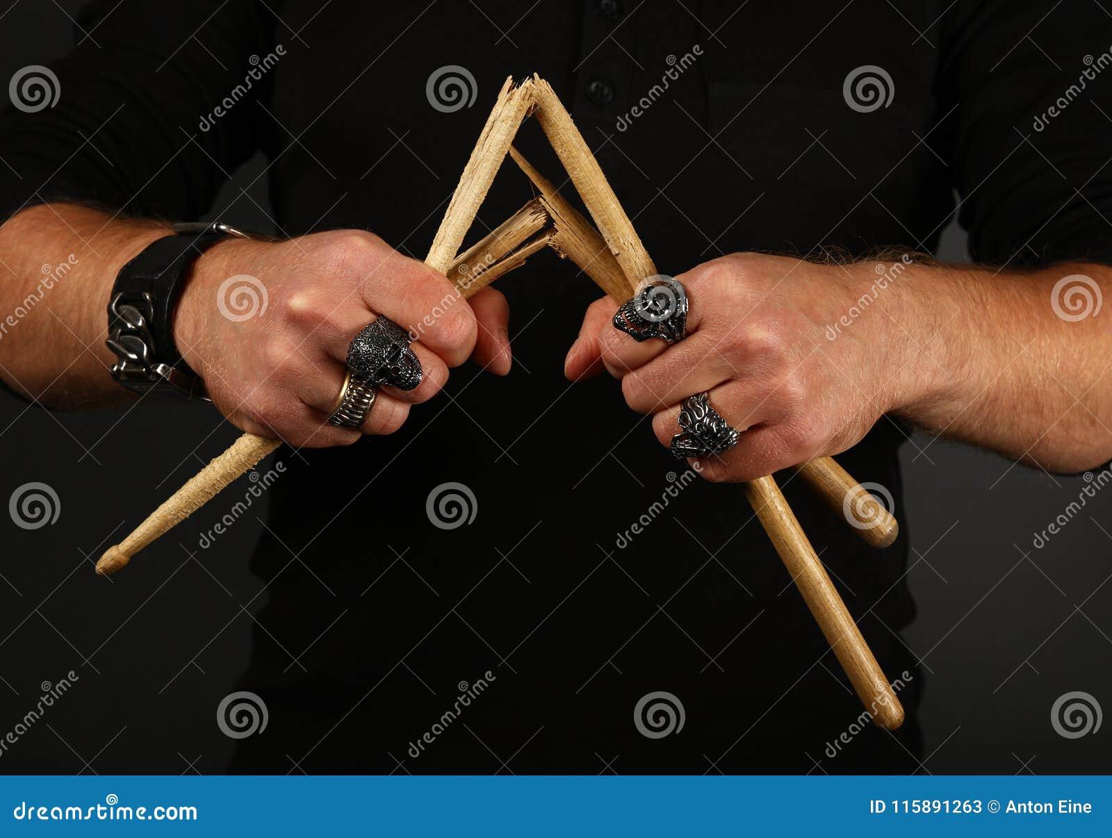 Mãos do homem com os pilões quebrados sobre o preto