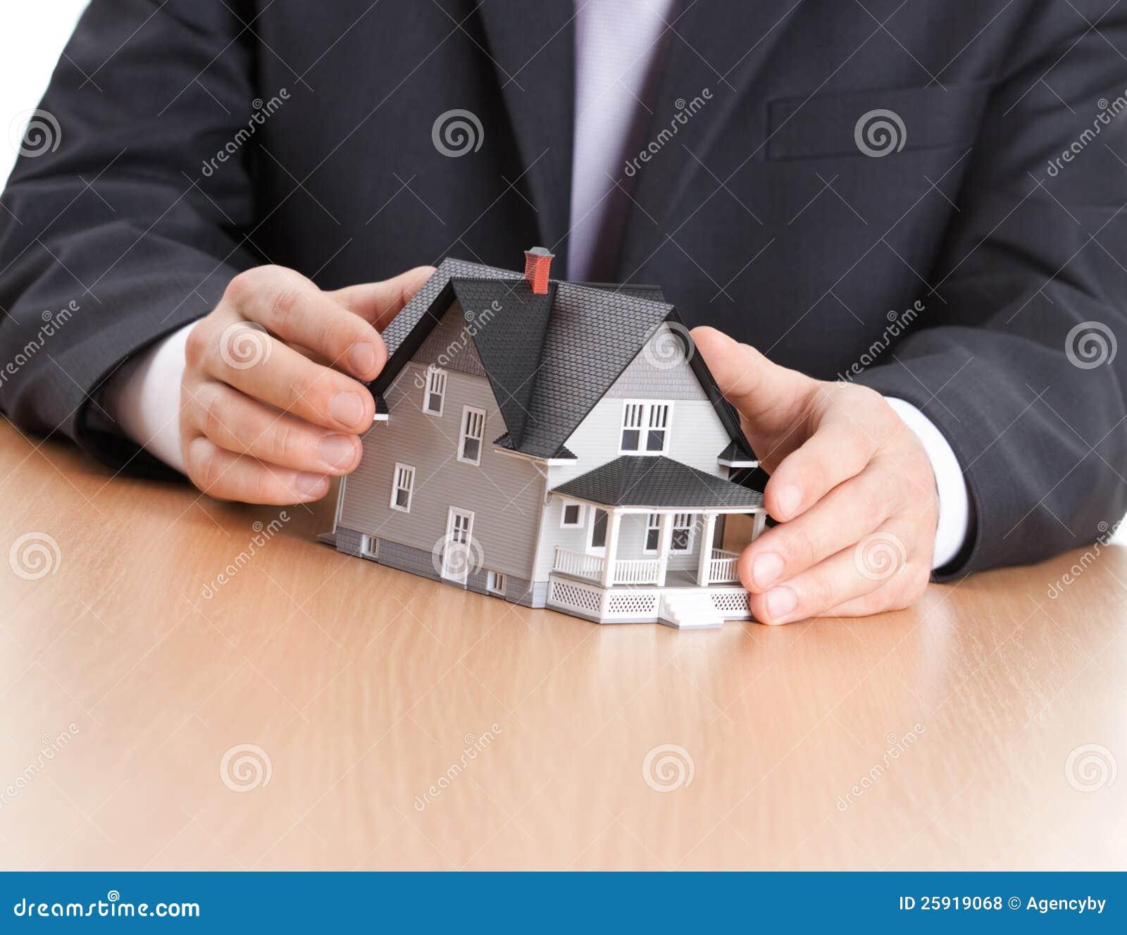 Mãos do homem de negócios em torno do modelo arquitectónico