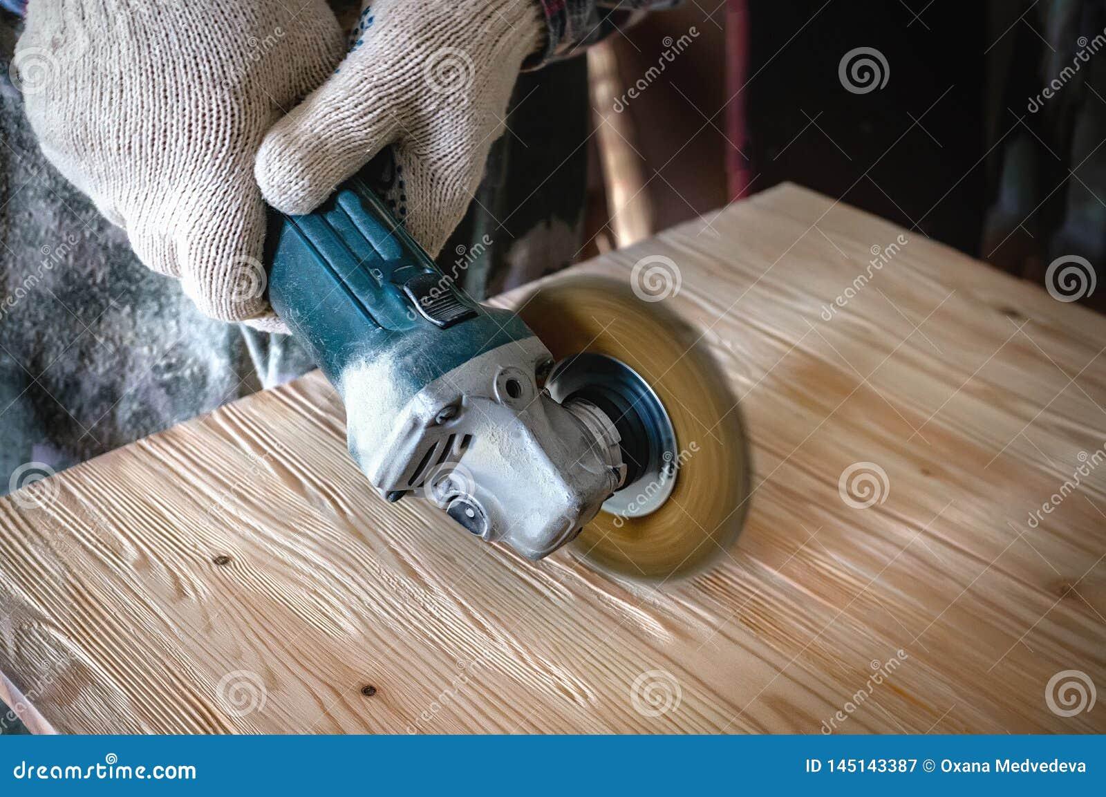M?os do mestre uma broca e uma escova para limpar a madeira e dar-lhe a textura O processo de escovar a madeira Copie o espa?o