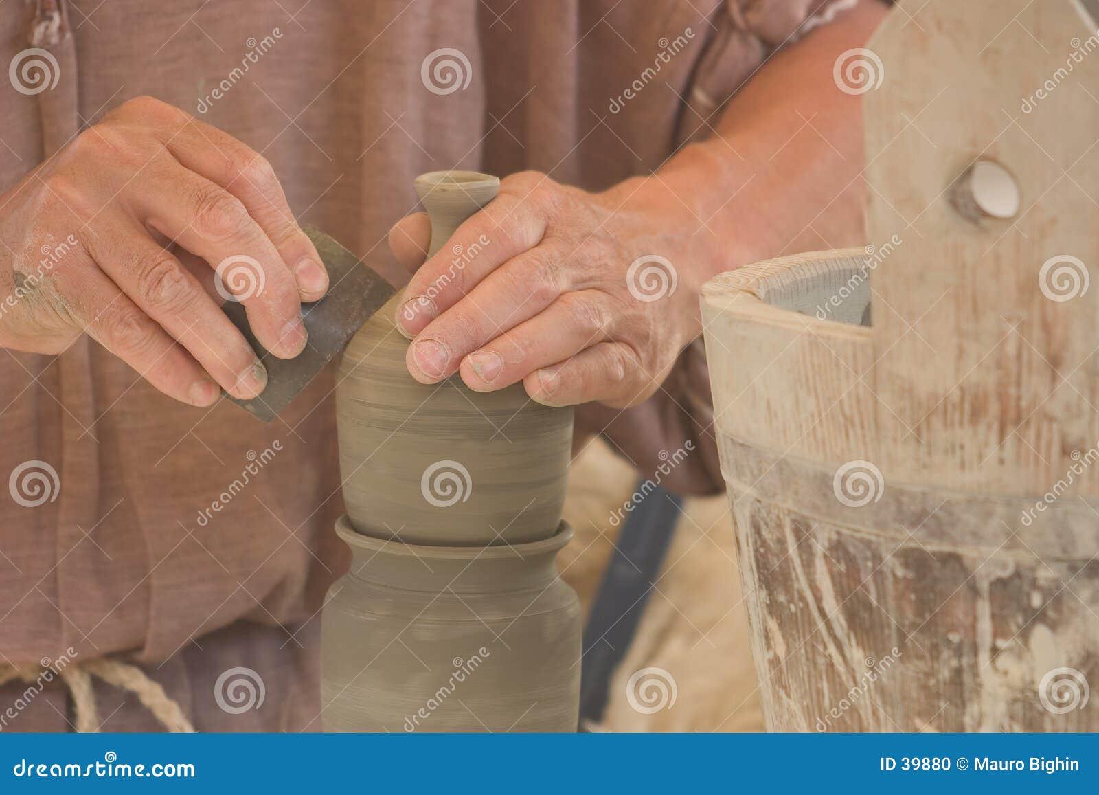 Mãos do oleiro no trabalho