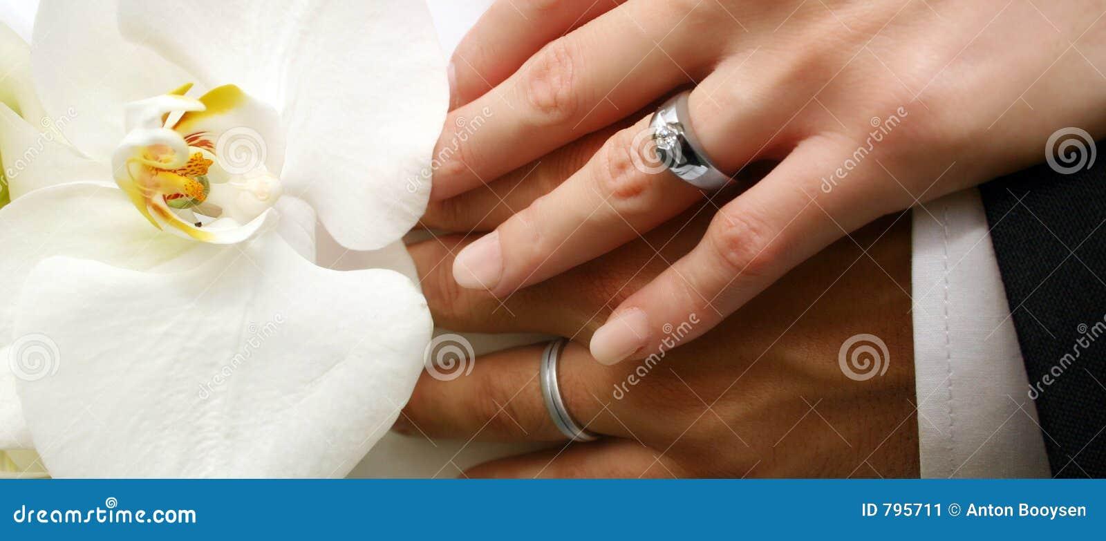 Mãos do par nupcial