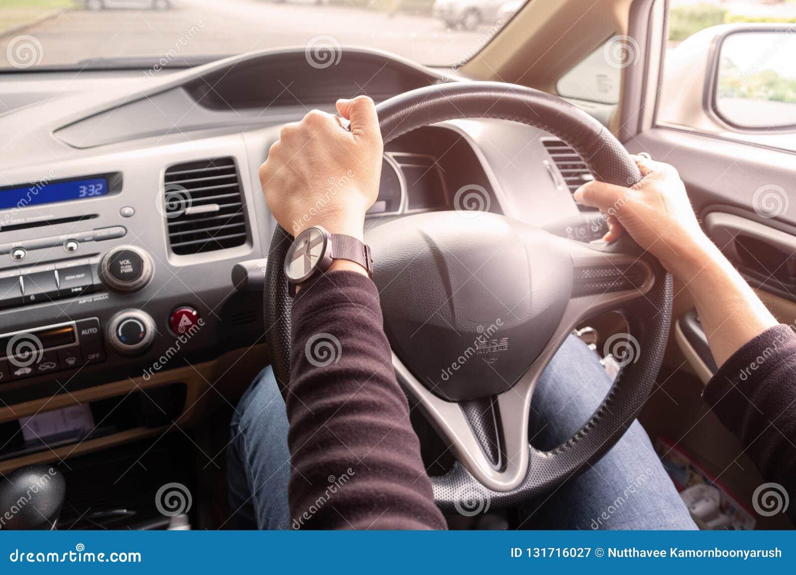 Mãos do ` s da mulher de um motorista no volante de um carro