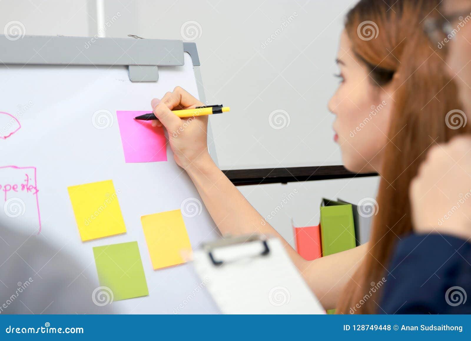 Mãos dos executivos asiáticos que explicam estratégias na carta de aleta na sala de conferências