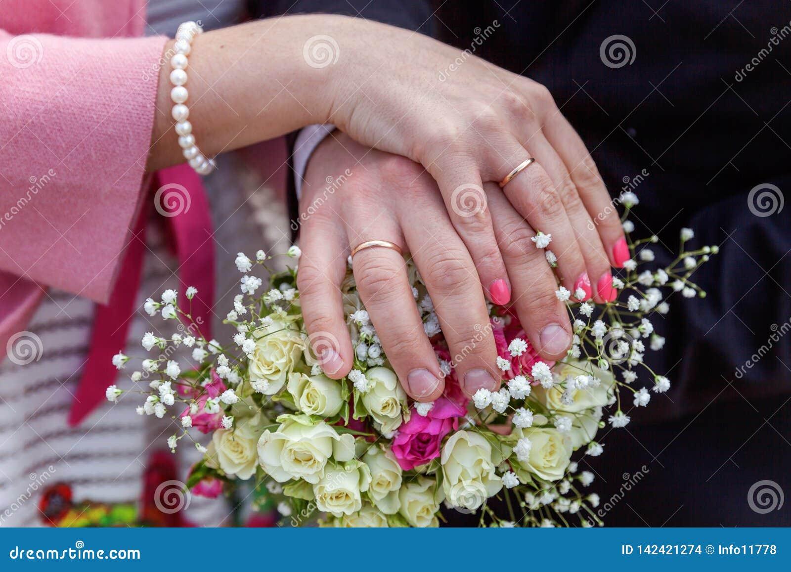 Mãos dos noivos com alianças de casamento contra o fundo do ramalhete nupcial das flores