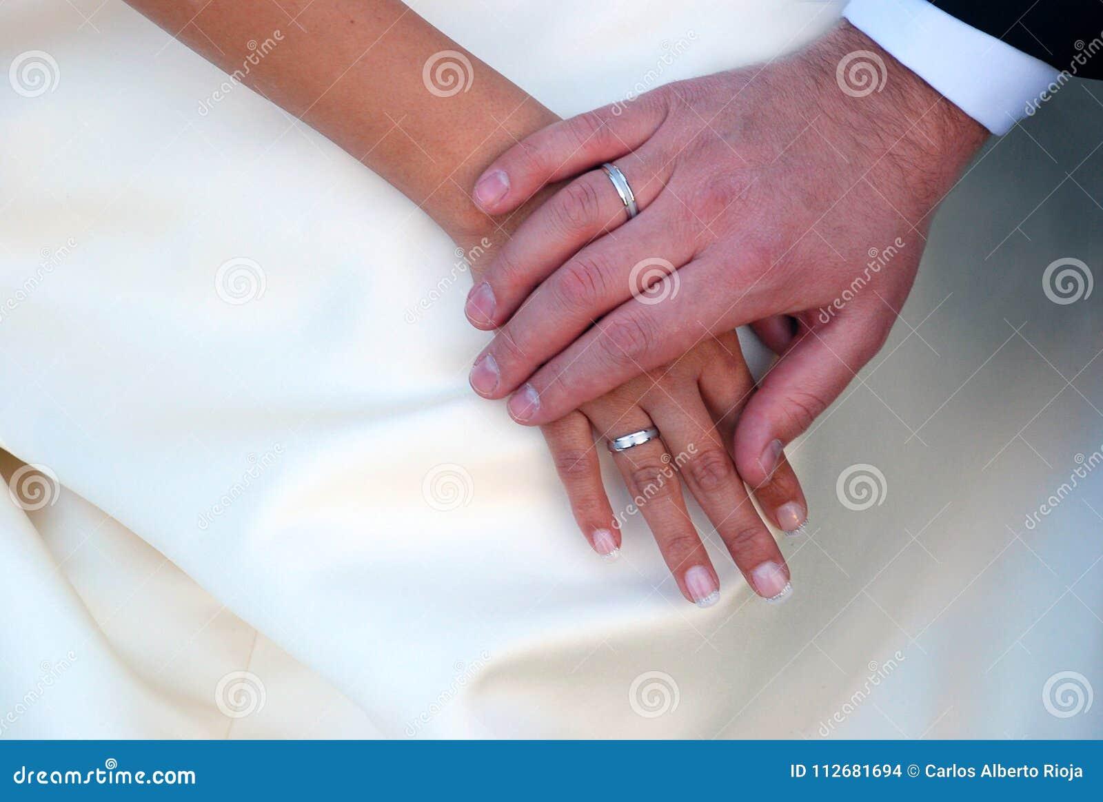 Mãos entrelaçadas com alianças de casamento