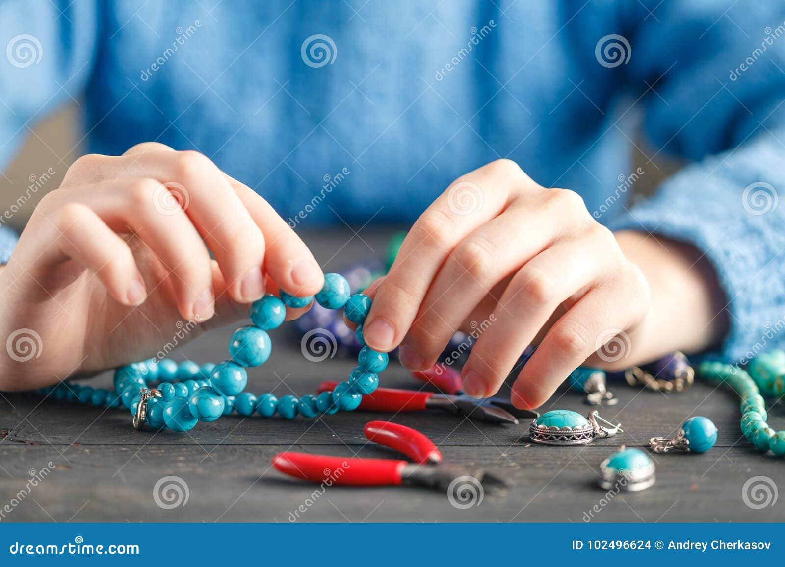 Mãos fêmeas com fabricação colorida da colar dos grânulos