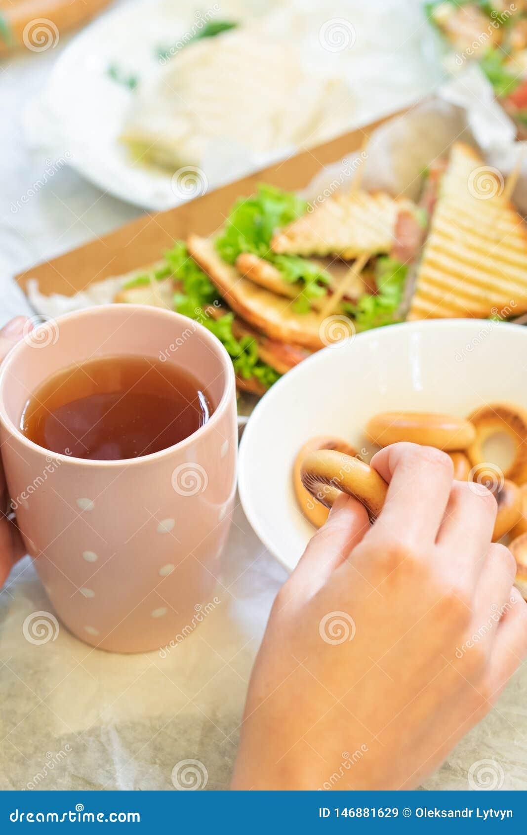 Mãos fêmeas com um copo do chá e dos bagels