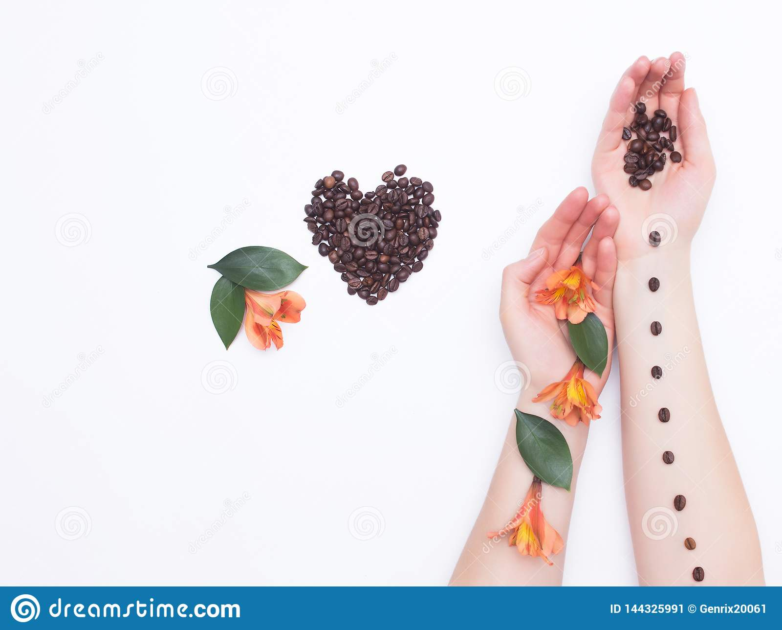 Mãos fêmeas em um fundo branco com feijões de café e flores do hibiscus, coração de feijões de café, aroma, conceito do amor